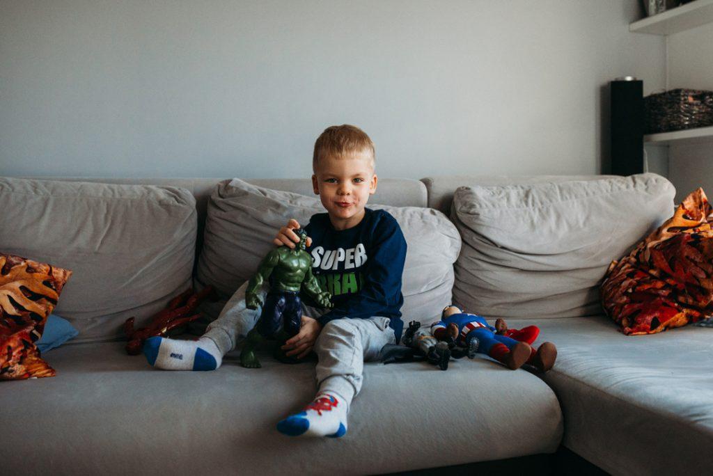 chłoiec z zabawkami na kanapie podczas sesji zdjęciowej