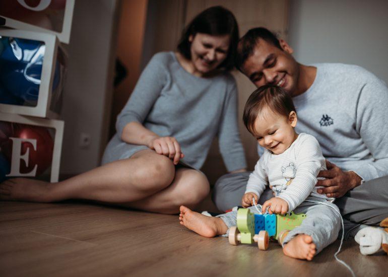 rodzice bawią się z dzieckiem fotografia rodzinna