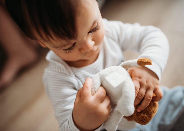 dziecko bawi sie maskotką fotografia rodzinna