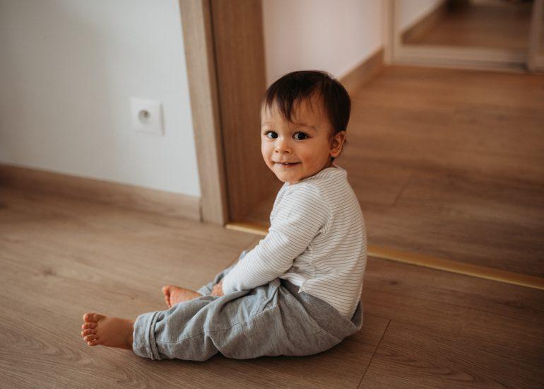 dziecko siedzi na podłodze w czasie sesji zdjęciowej