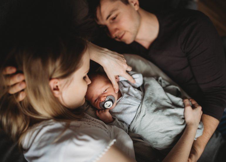 rodzina z noworodkiem na łóżku