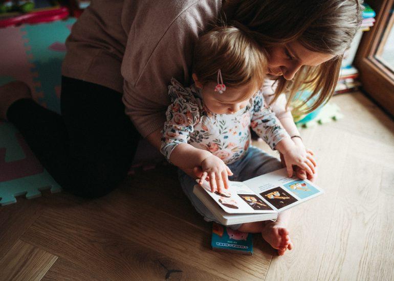 mama z córką czyta książkę w czasie sesji zdjęciowej lifestyle